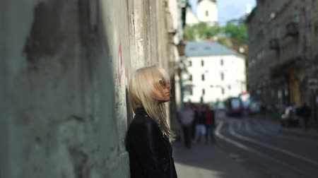 coquettish : Beautiful blonde girl standing near the old wall in the city centre