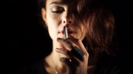 papieros : Woman smoking a cigarette coming out of the dark Wideo