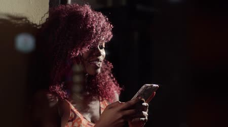 черные волосы : The sensitive close-up portrait of the happy and smiling afro-american woman with red curly hair typing messages to her friend in the dark vantage cafe; then calling to the friend to have a friendly