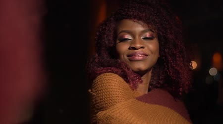 black yellow : The charming sight of the afro-american girl wrapped in the yellow knitted plaid and enjoying the evening in the cafe Stock Footage
