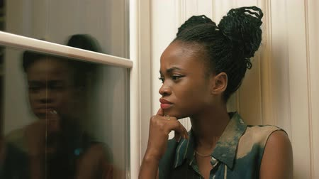 elszigetelt fekete : Close-up side portrait of the trendy-dressed moody afro-american woman with african pigtails looking through the window and forward Stock mozgókép