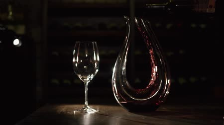 ne : The horizontal composition of the hand pouring the red wine into the decanter placed ner the glass wine on the table.