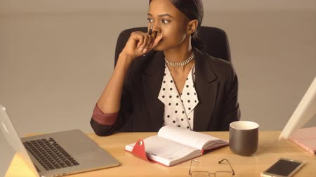 profi : Thoughtful black woman writes something sitting at office table