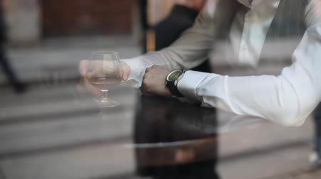 lux : The close-up portrait of the hands of man holding the glass with cognac. The man is dressed in stylish suit and wearing the hand watch. Stock Footage