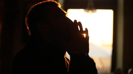 repentance : The close-up side portrait of the upset man keeping his hands in the sign for pray at the background of the sunset. Stock Footage