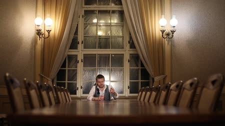 wasted : The horizontal portrait of the stylish depressed businessman pouring whiskey into the glass and drinking it. The aristocratic interior of the room. Stock Footage