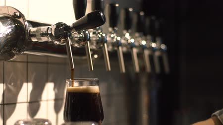 beer tap : Close-up view of the barman`s hand filling the glass with the dark beer using the draft beer tower at the white background.