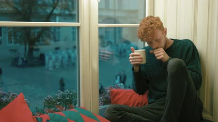 плохо : The ill blond curlyhead boy drinking hot tea, coughing and sitting on the window-sill of the cafe. He is surrounded by cushions Стоковые видеозаписи