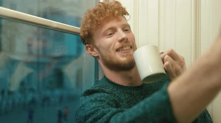 плохо : The portrait of the man with blond curly hair taking smiling and serious selfies with a cup of hot tea
