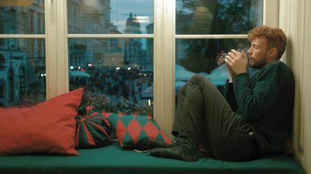 плохо : The horizontal photo of the ill man with blond hair holding the cup of hot tea, drinking it. He is sitting on the soft green window-sill surrounded by colorful cushions and looking through the window