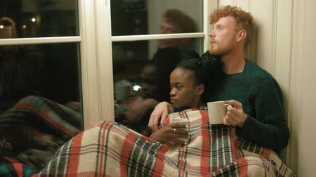 pléd : Lovely couple wrapped in red plaid on the window-sill. Afro-american girl is holding the white cup and the man with blond curly hair and beard is drinking the hot tea. Horizontal side portrait