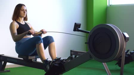 evezés : The side portraif of the woman stretching her boy on the rowing machine in the green gym.