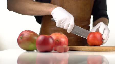cutting up : The fruit composition consisted of apples and pomegranate. The man is cutting the red apple. Stock Footage