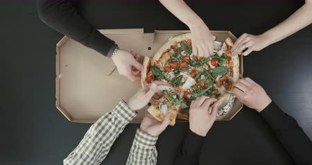 peperoni : The close-up top view of the hands of four friends taking pieces of pizza.
