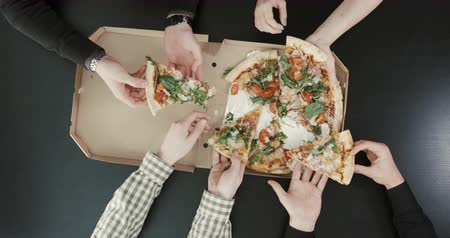 peperoni : Above view of hands taking pazza. Box placed on the dark table. Friends eating pizza. Stock Footage