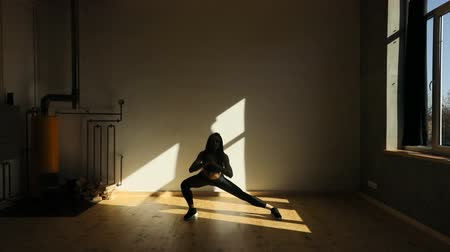 плохо : The young sportwoman is doing side lunges in the badly lighted studio.