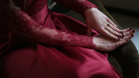 coffer : Close-up view of the hands with ring of the married woman in red. She is stroking her hands and the ring.