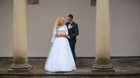 architektura : Groom comes to blonde bride standing alone between the columns Wideo