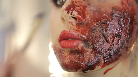 Make-up artist make the girl halloween make up in studio.Halloween face art.Woman applies on professional greasepaint on the face of spanish girl.War-paint with blood, scars and wounds. Stock Footage