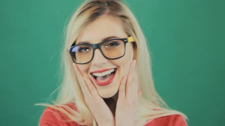потрясенный : Cute Blonde in Fashional Glasses Grimacing on Green Background in Studio. Closeup Portrait of Young Surprised Woman with Red Sensual Lips.