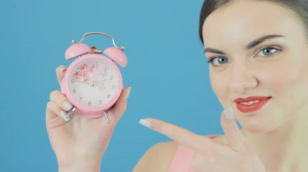 потрясенный : Closeup Portrait of Smiling Cute Brunette with Pink Clock in Hand on Blue Background in Studio. Time Concept. Стоковые видеозаписи
