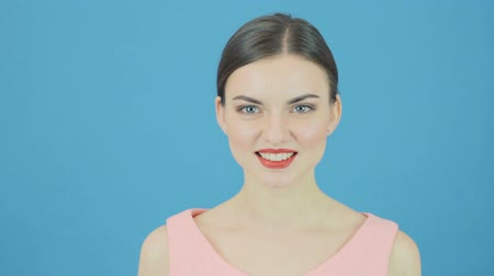 зубастая улыбка : Portrait of Smiling Beautiful Woman with Perfect Fresh Clean Skin. Youth and Skin Care Concept. Isolated on Blue Background in Studio. Стоковые видеозаписи