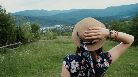 Back View of Woman Wearing Summer Hat and Looking on the Mountans During Her Vacation on the Countryside.