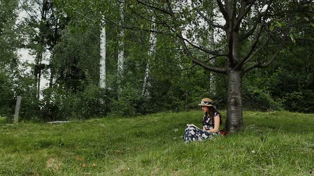 Relaxed Young Woman is Reading a Book Under the Tree Shadow During Summer Vacation on the Countryside.