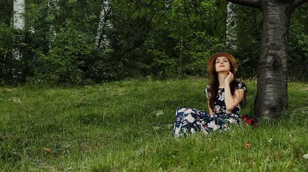 Pretty Girl Wearing Summer Hat and Dark Long Dress is Sitting Under the Tree with Book in Hands and Listening the Music During Her Vacation on the Countryside.