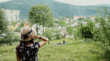 Back View of Amazing Girl in Summer Hat and Dress on Countryside Background. Woman Turns Around and Looks at the Camera. Стоковые видеозаписи