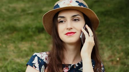 Outdoors Closeup Portrait of Pretty Girl with Summer Hat Using Her Mobile Phone and Smiling.