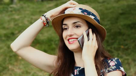 Portrait of Attractive Young Woman with Summer Hat Using Her Smartphone and Smiling Outdoors.