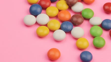 Close Up of a Pile of Colorful Chocolate Coated Candy on Pink Background. Стоковые видеозаписи