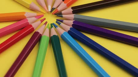 Colored Pencils Lying on Bright Yellow Background in a Circle. Стоковые видеозаписи