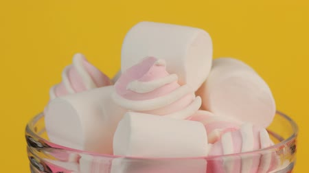 Pink Twisted and White Marshmallow in a Glass Jar on a Yellow Background.