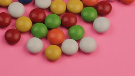 Close Up of a Pile of Colorful Chocolate Coated Candy on Pink Background