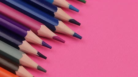 Many Different Colored Pencils Lying on Pink Background in a Wave Стоковые видеозаписи