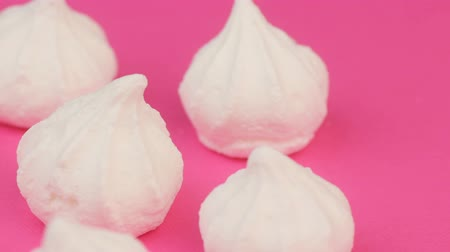Top View of White Mini Marshmallows on Pink Background
