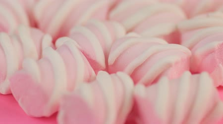 Top View of Many Different Twisted Marshmallow on Pink Background. Winter Food Concept.