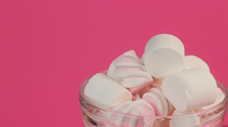 Different Fluffy Sweet Marshmallows in a Glass Bowl on Pink Background.