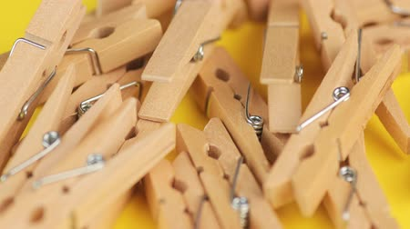 Wood Natural Bamboo Clothespins on Yellow Background.