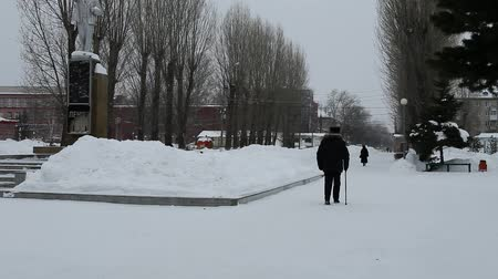 An elderly man walks around the city park in the winter. In one hand stick. on the left there is a monument.