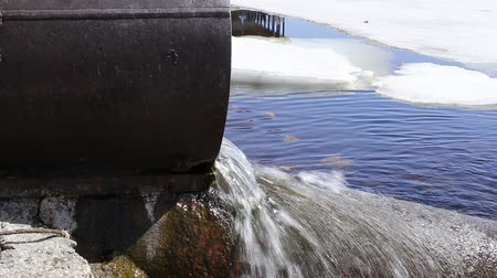gushing : A large, old trumpet made of iron. From it flows water into the river. sometimes dirty and harmful. Stock Footage