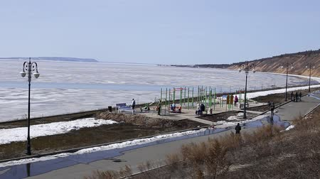 a sports field on the background of a river. water and ice. there are people present and playing. far away mountains and sky.