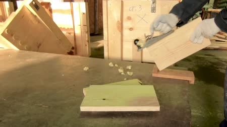 Worker planes the board in production. Hands close up. In the background is a model of wood. Stok Video
