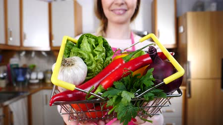Happy woman holding shopping basket with vegetables 影像素材