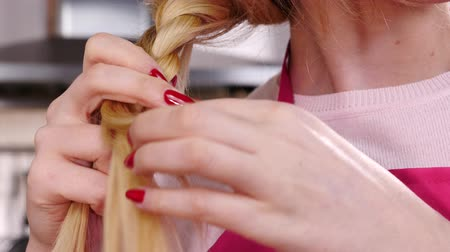Woman making tying up braid hair.
