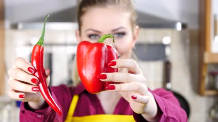 Woman choosing between chilli and bell pepper