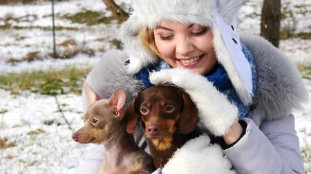 Woman playing with her little dogs outside winter