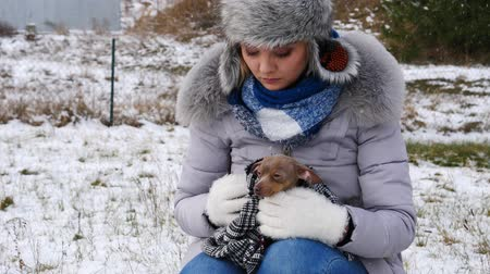 Worried woman taking care of small dog during winter
